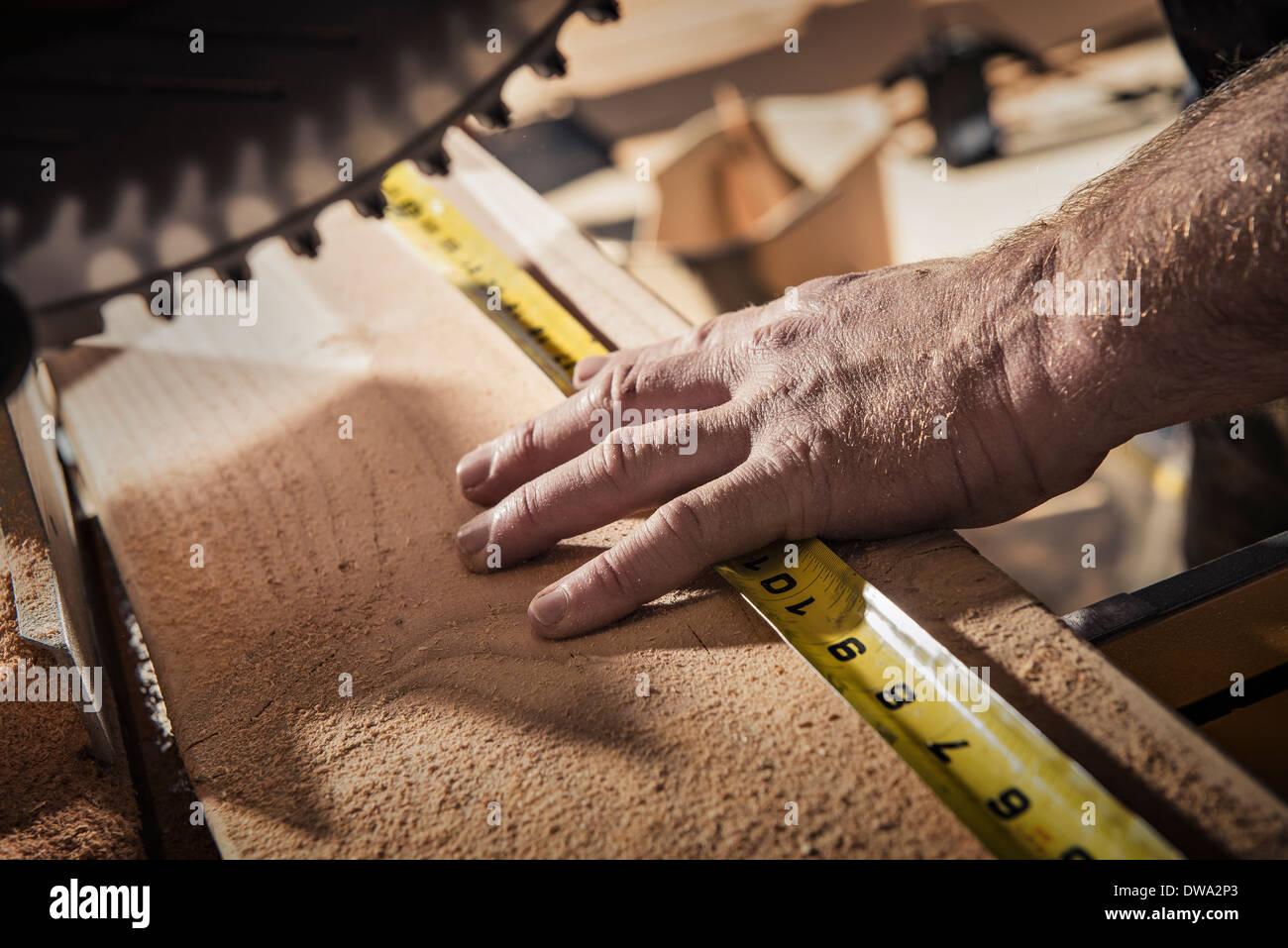 Cerca de carpintero macho utilizando cinta de medir en el taller Imagen De Stock
