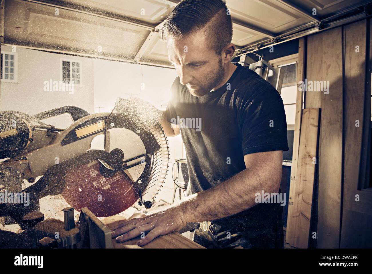 Carpintero macho aserrado tablón de madera en el taller Imagen De Stock