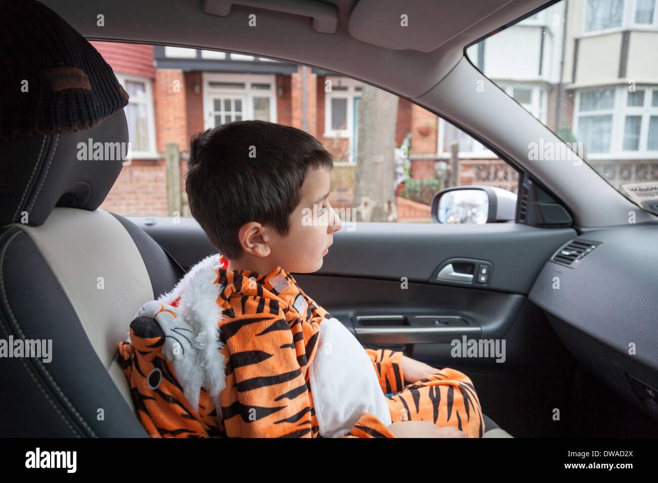 Niño sentado en un coche ,vestida con traje de tigre Imagen De Stock