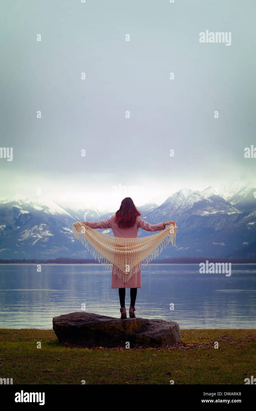 Una mujer con un abrigo rosa con un chal blanco está de pie en un lago Imagen De Stock