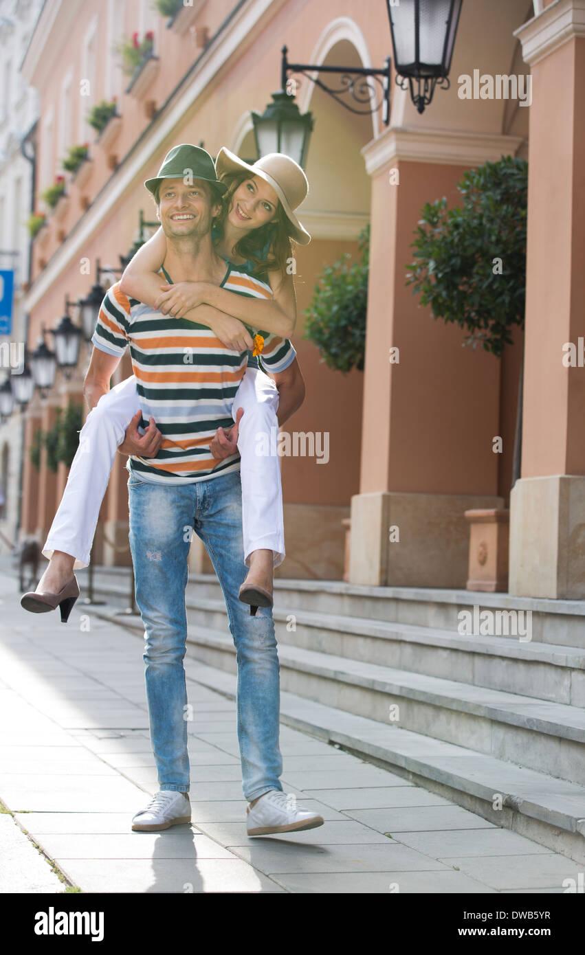 Joven dando piggyback ride a mujer en la acera frente al edificio Foto de stock