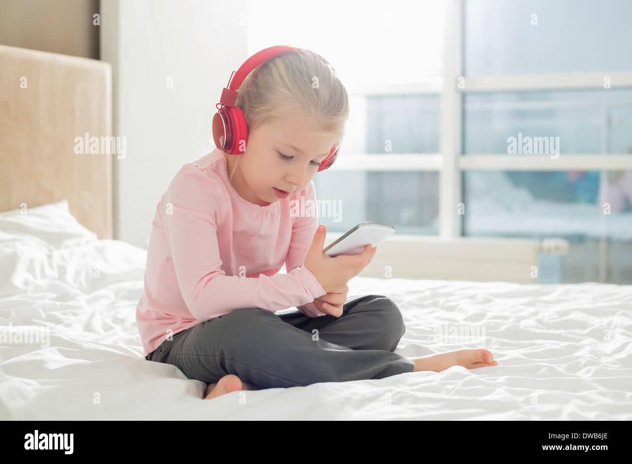 La longitud completa de la niña escucha música con los auriculares en el dormitorio Imagen De Stock