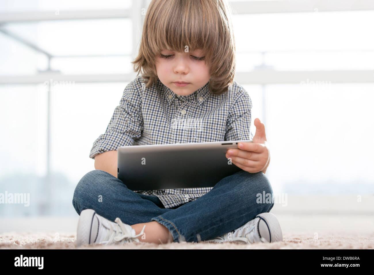 La longitud total del niño mediante tableta digital en el salón Imagen De Stock