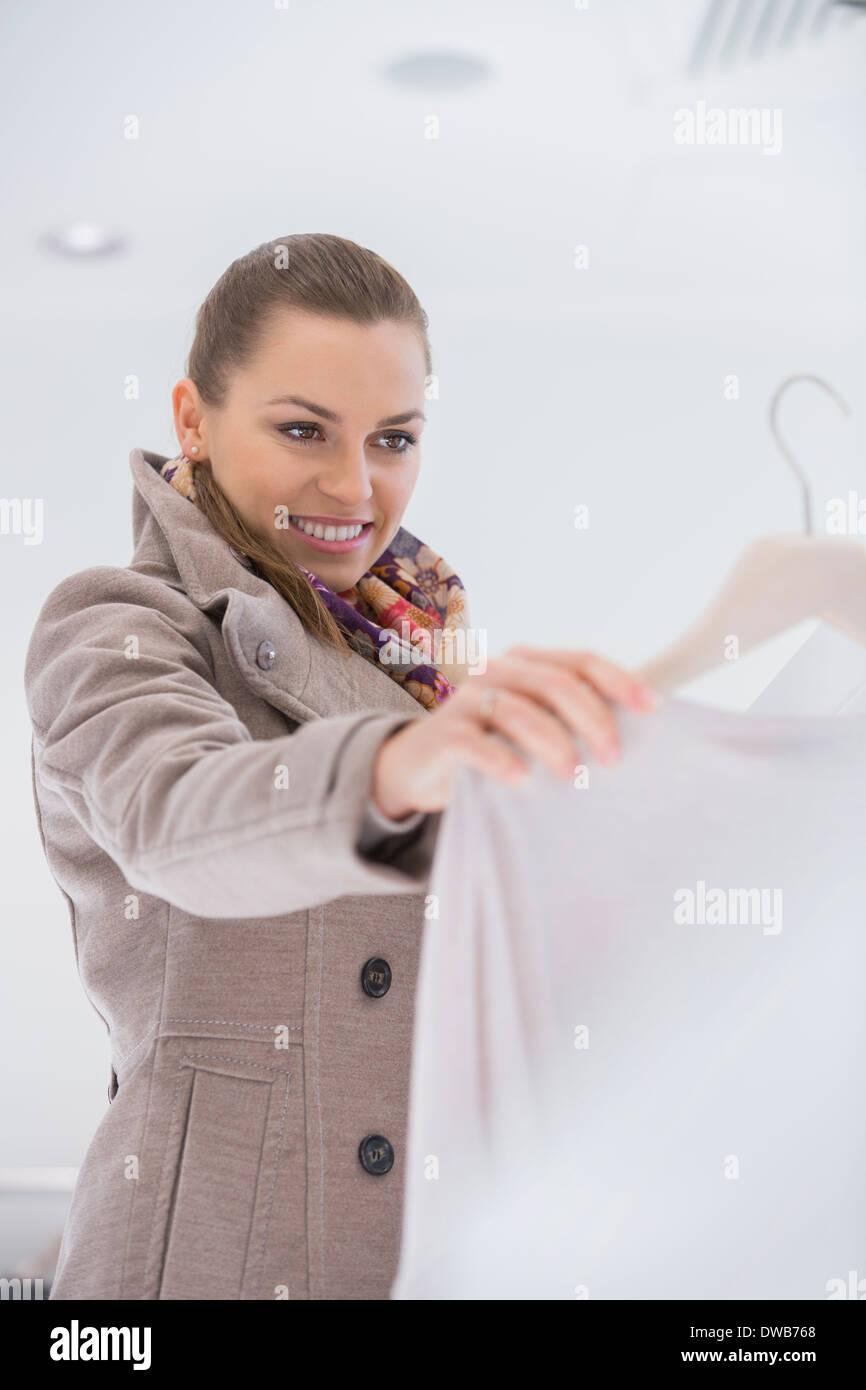 Feliz joven elegir suéter en la tienda Imagen De Stock