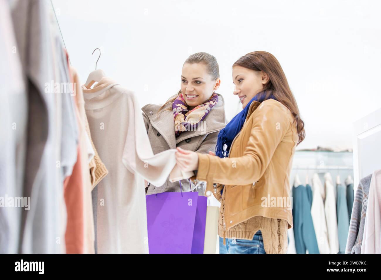 Amigas jóvenes eligiendo suéter en la tienda Imagen De Stock