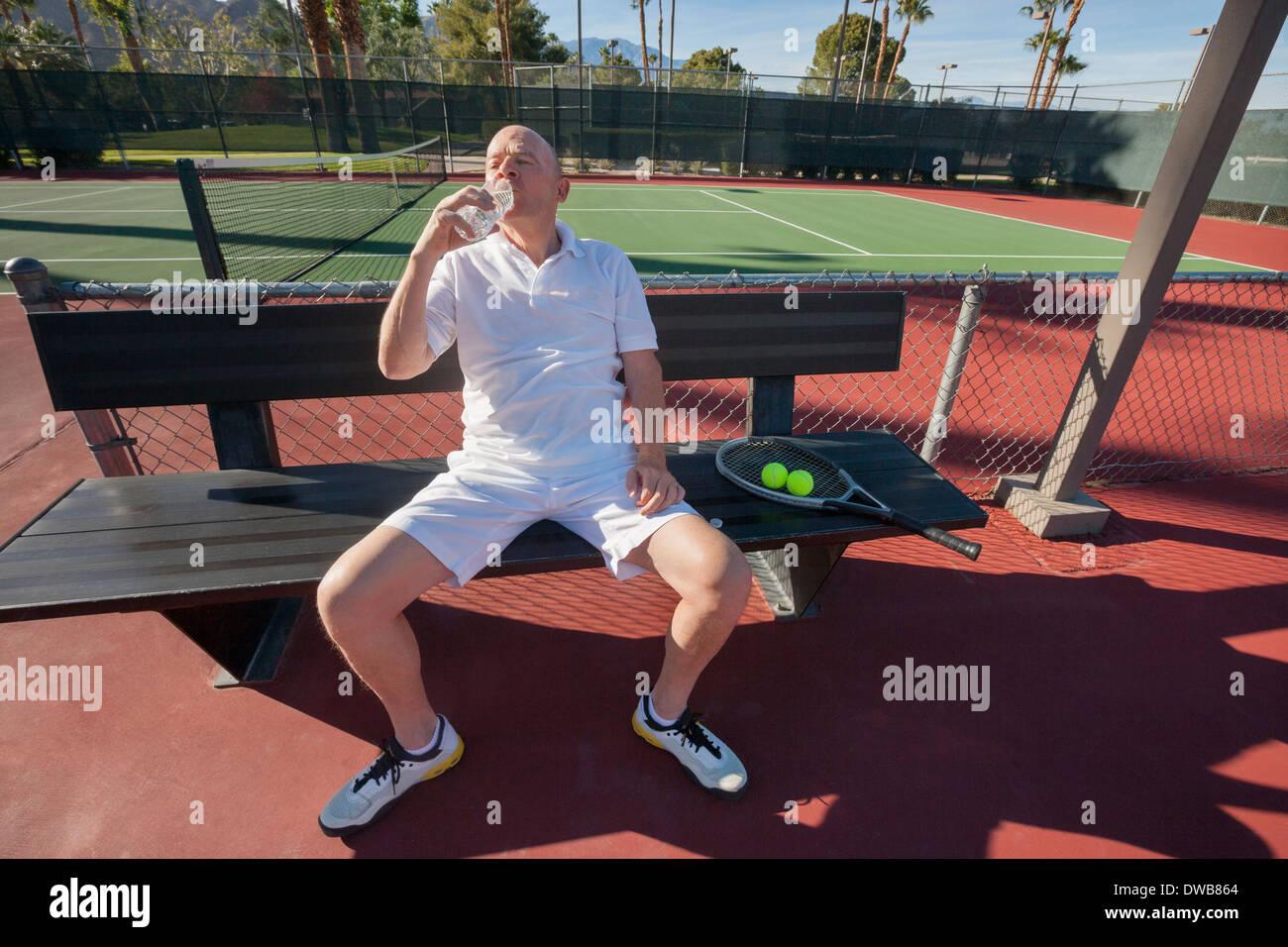 Jugador de tenis masculino senior de agua potable mientras se relaja en la corte Imagen De Stock