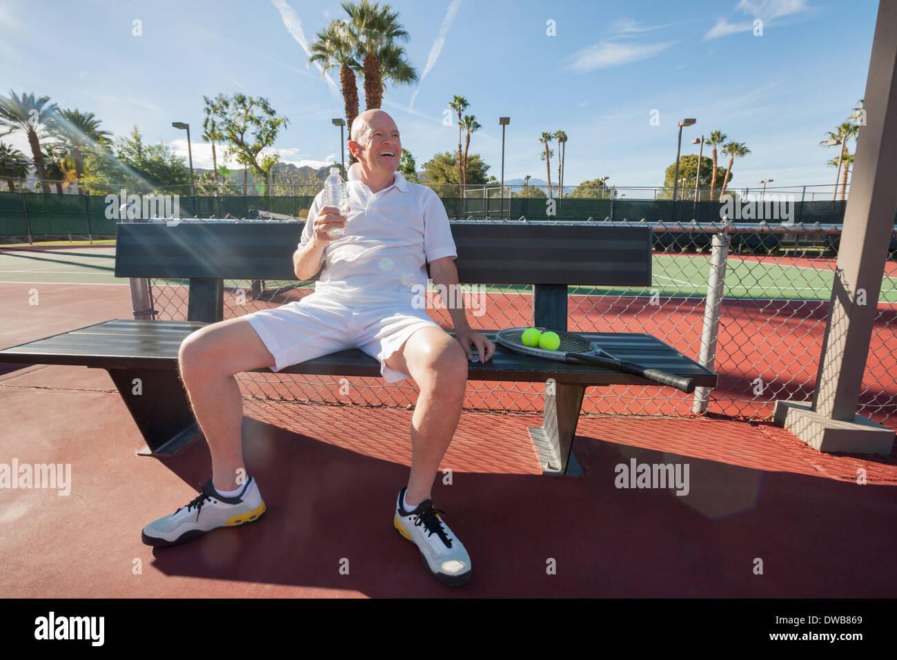 Jugador de tenis masculino senior feliz con la botella de agua sentados en un banco en la corte Imagen De Stock