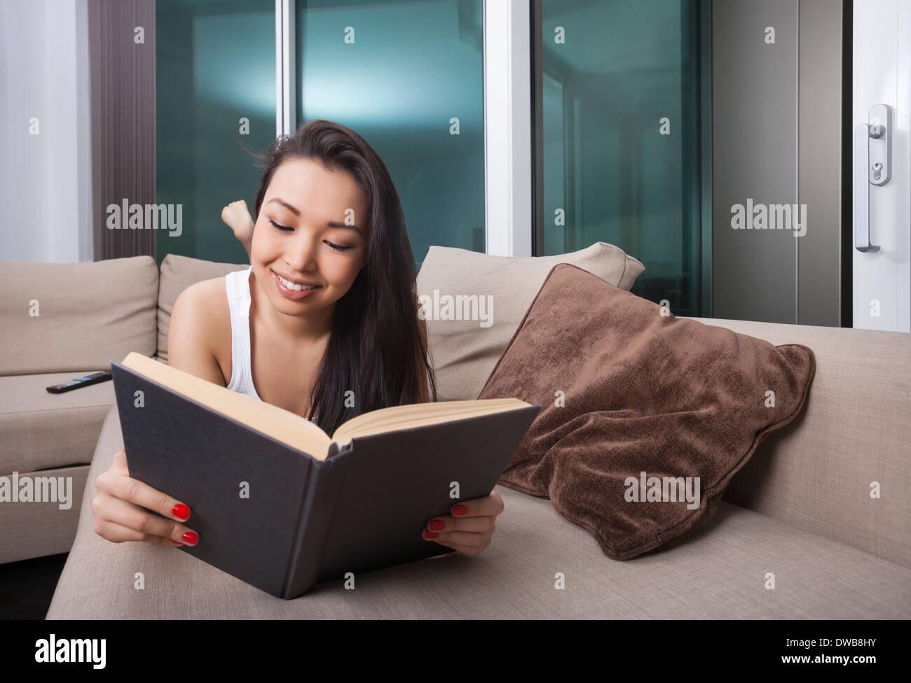 Feliz joven libro de lectura mientras está acostada sobre el sofá Foto de stock