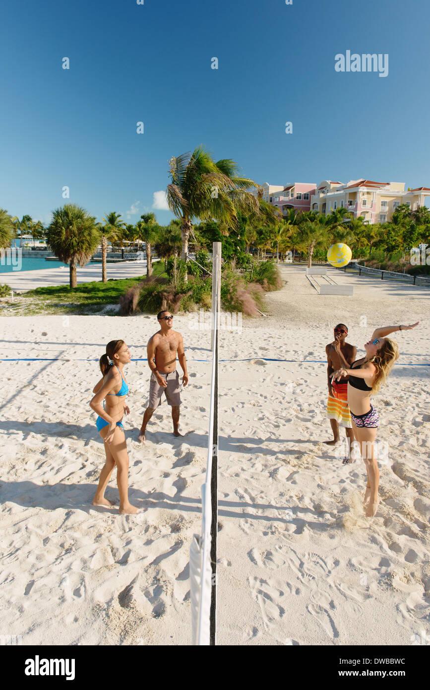 Cuatro jóvenes amigos adultos jugando voleibol de playa, Providenciales, Islas Turcas y Caicos, Caribe Imagen De Stock