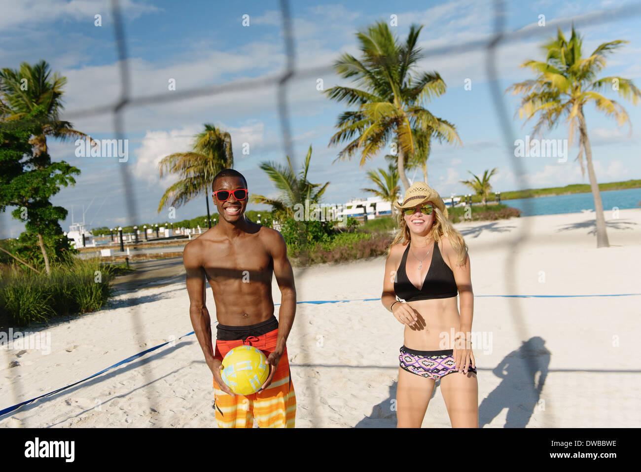 Dos jóvenes amigos adultos jugando voleibol de playa, Providenciales, Islas Turcas y Caicos, Caribe Imagen De Stock