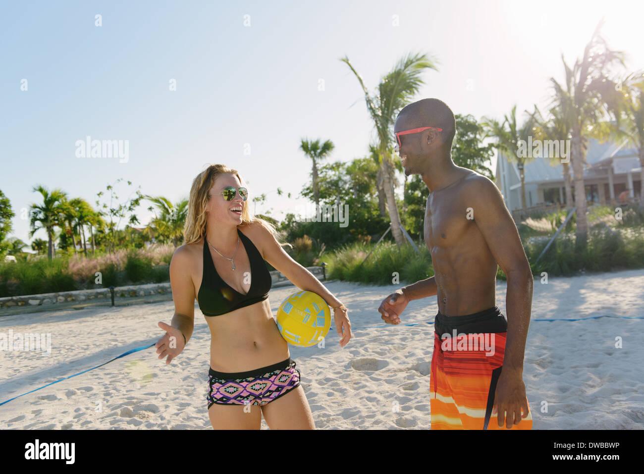 Dos jóvenes amigos adultos con voleibol de playa, Providenciales, Islas Turcas y Caicos, Caribe Imagen De Stock