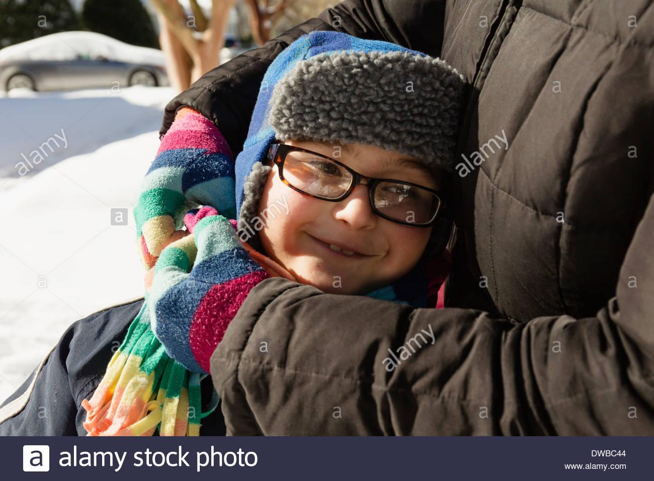 Abrazarse madre hijo vestidos de invierno gorra y gafas Foto de stock