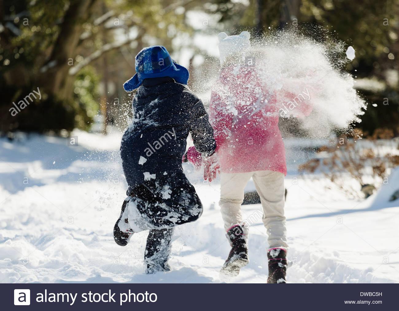Dos niños corriendo en la nieve Imagen De Stock