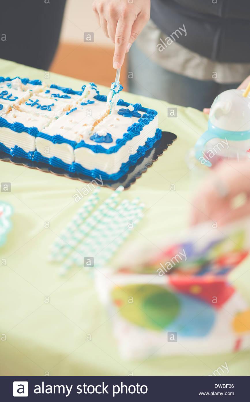 Cerca de mujer madura rebanar el pastel de cumpleaños Imagen De Stock