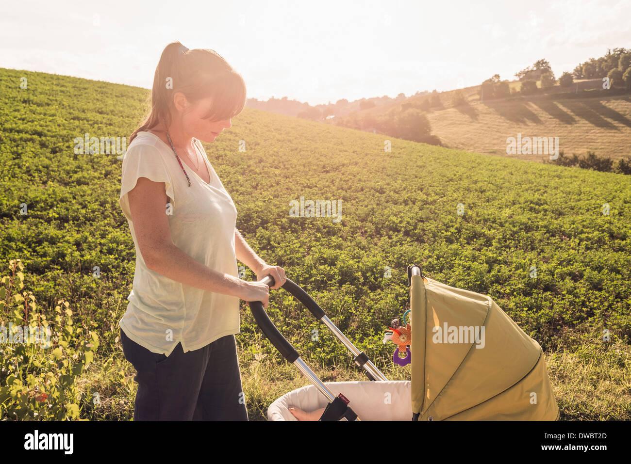 Madre paseando en el campo empujando cochecito de bebé Foto de stock