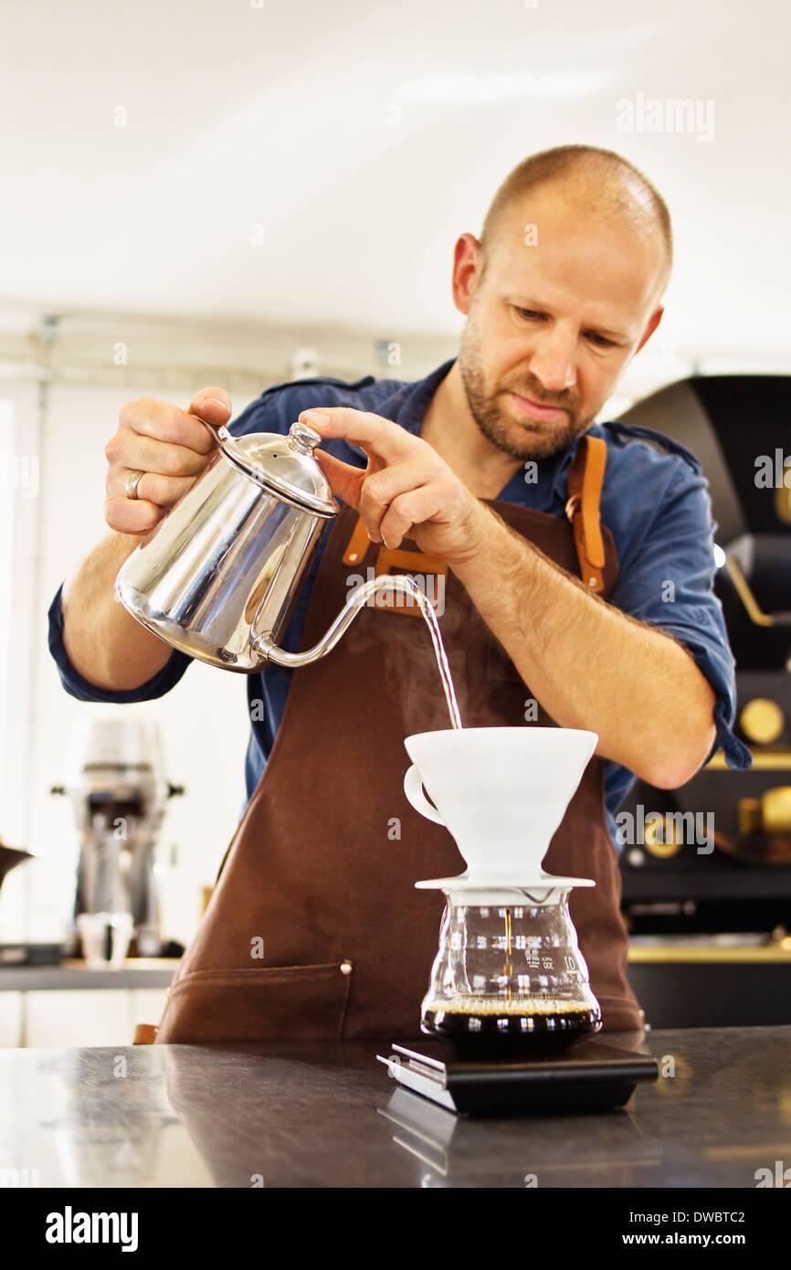 Barista vertiendo agua hirviendo en un filtro de café Foto de stock