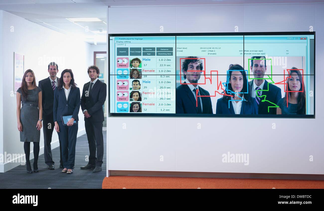 Retrato de trabajadores de oficina de pie junto al sistema de software de reconocimiento facial Imagen De Stock