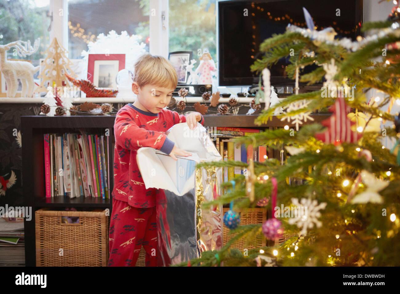 Joven desembalaje de regalo en Navidad Imagen De Stock