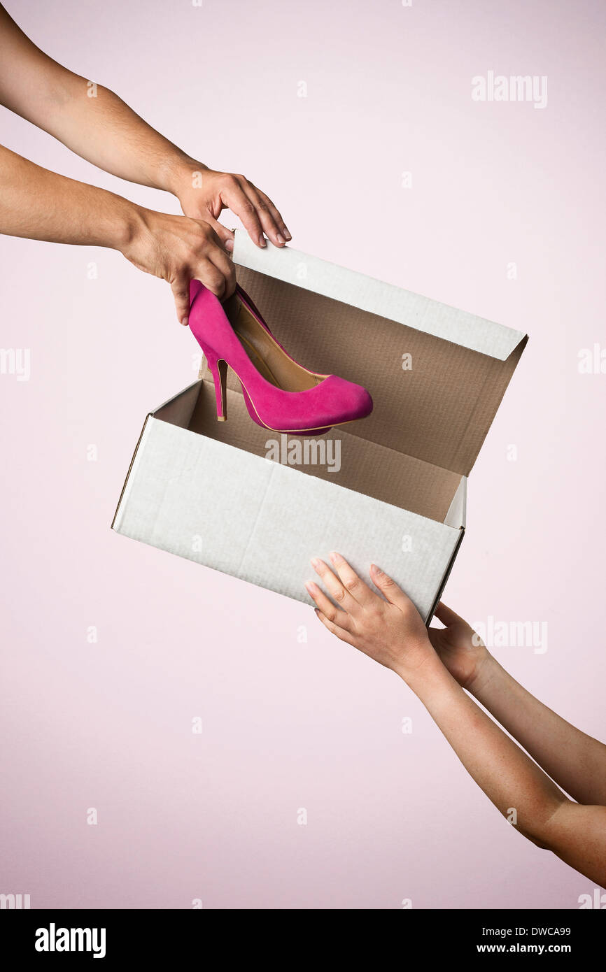 Foto de estudio entrega caja de zapatos con zapatos de tacón alto rosa Imagen De Stock