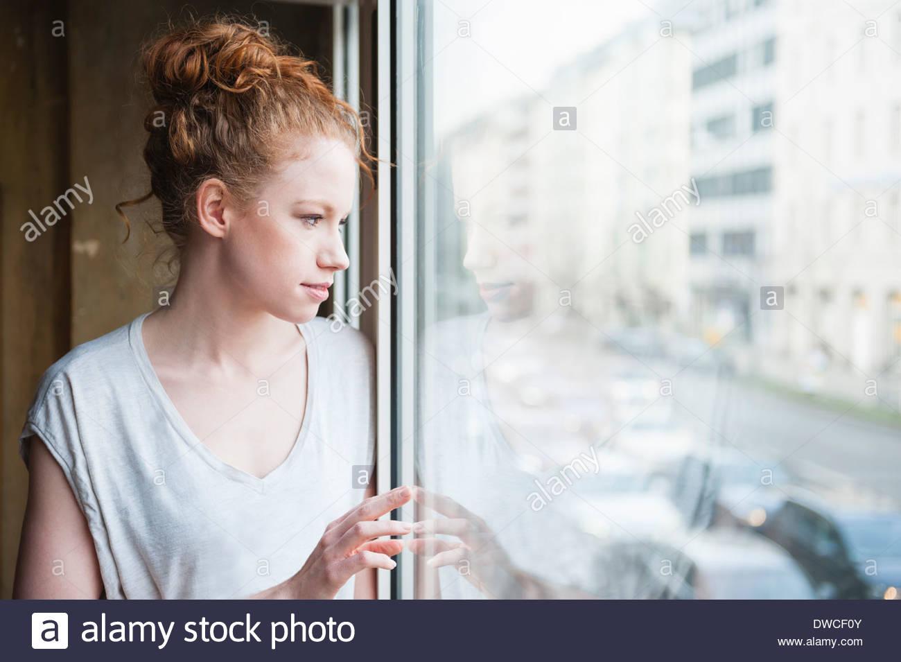 Mujer joven mirando hacia afuera de la ventana a la calle Imagen De Stock
