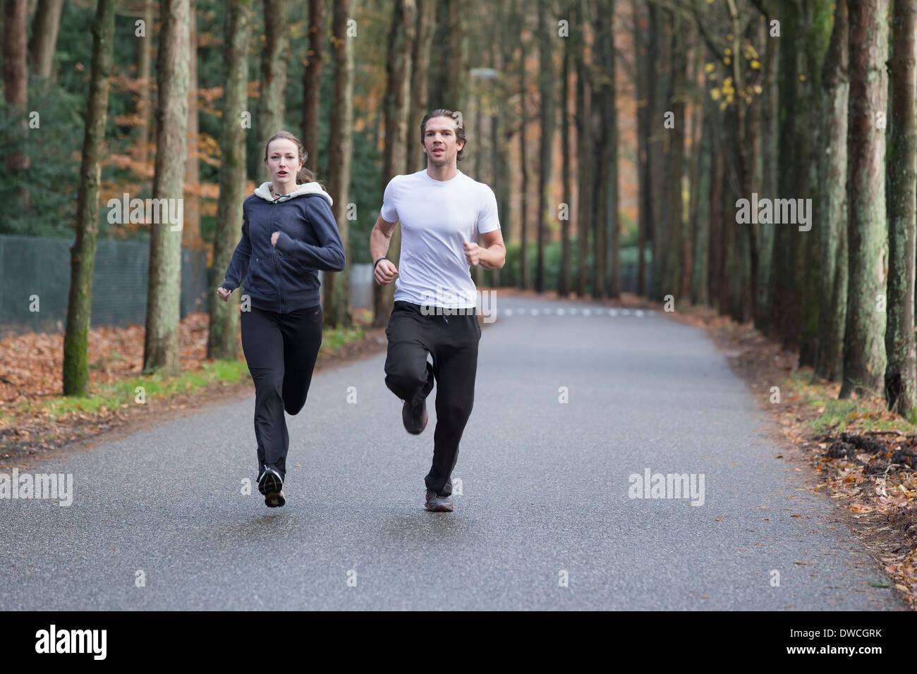 Par corriendo a través del bosque Imagen De Stock