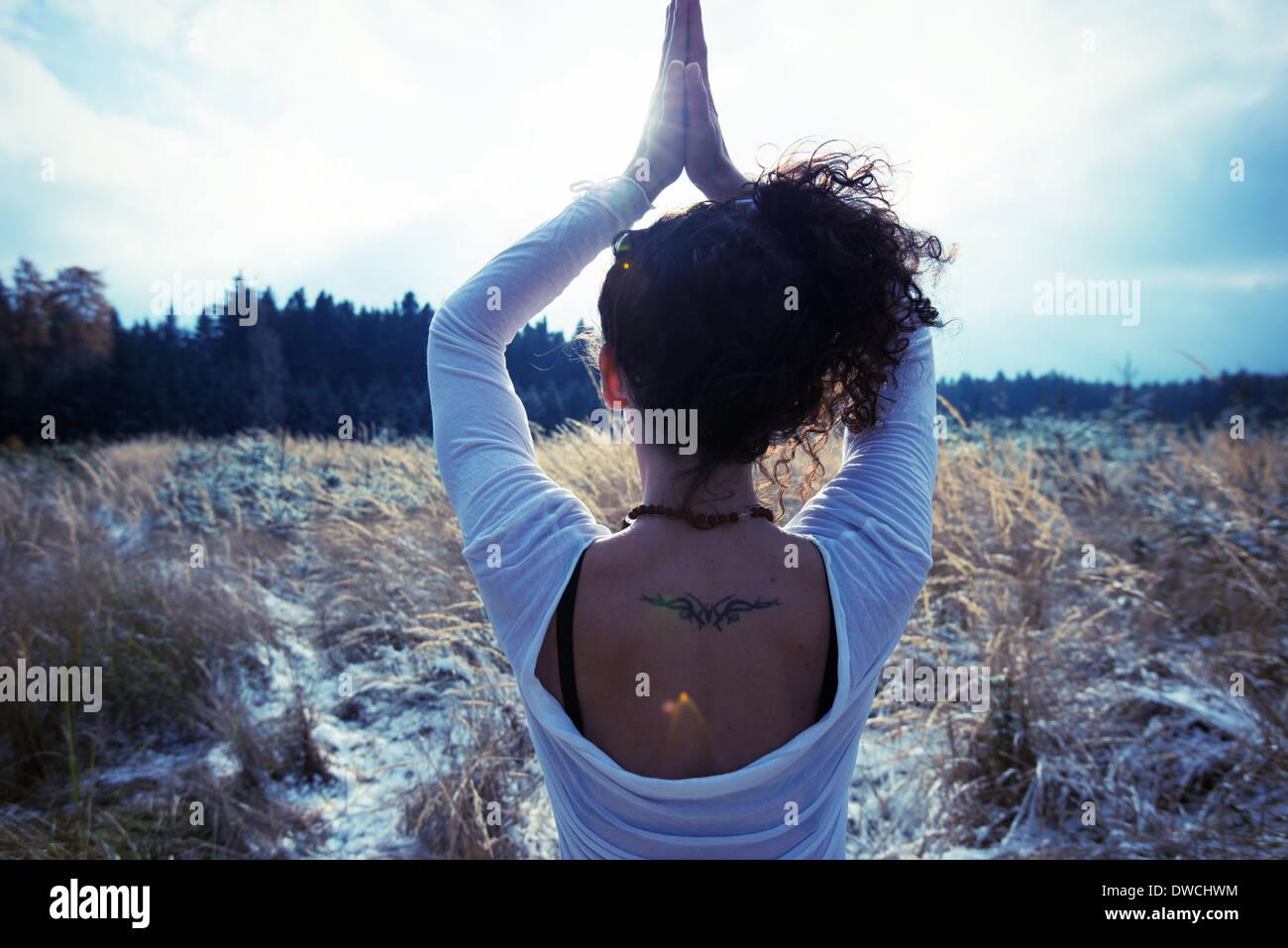 Mitad mujer adulta practicando yoga árbol permanente plantean Imagen De Stock