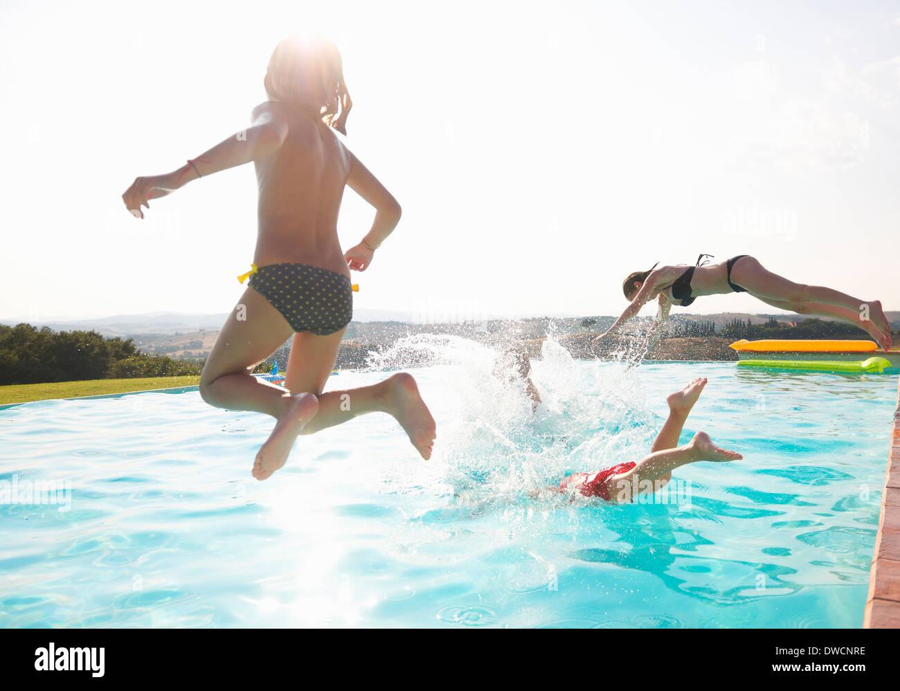 Tres personas saltando en la piscina Imagen De Stock