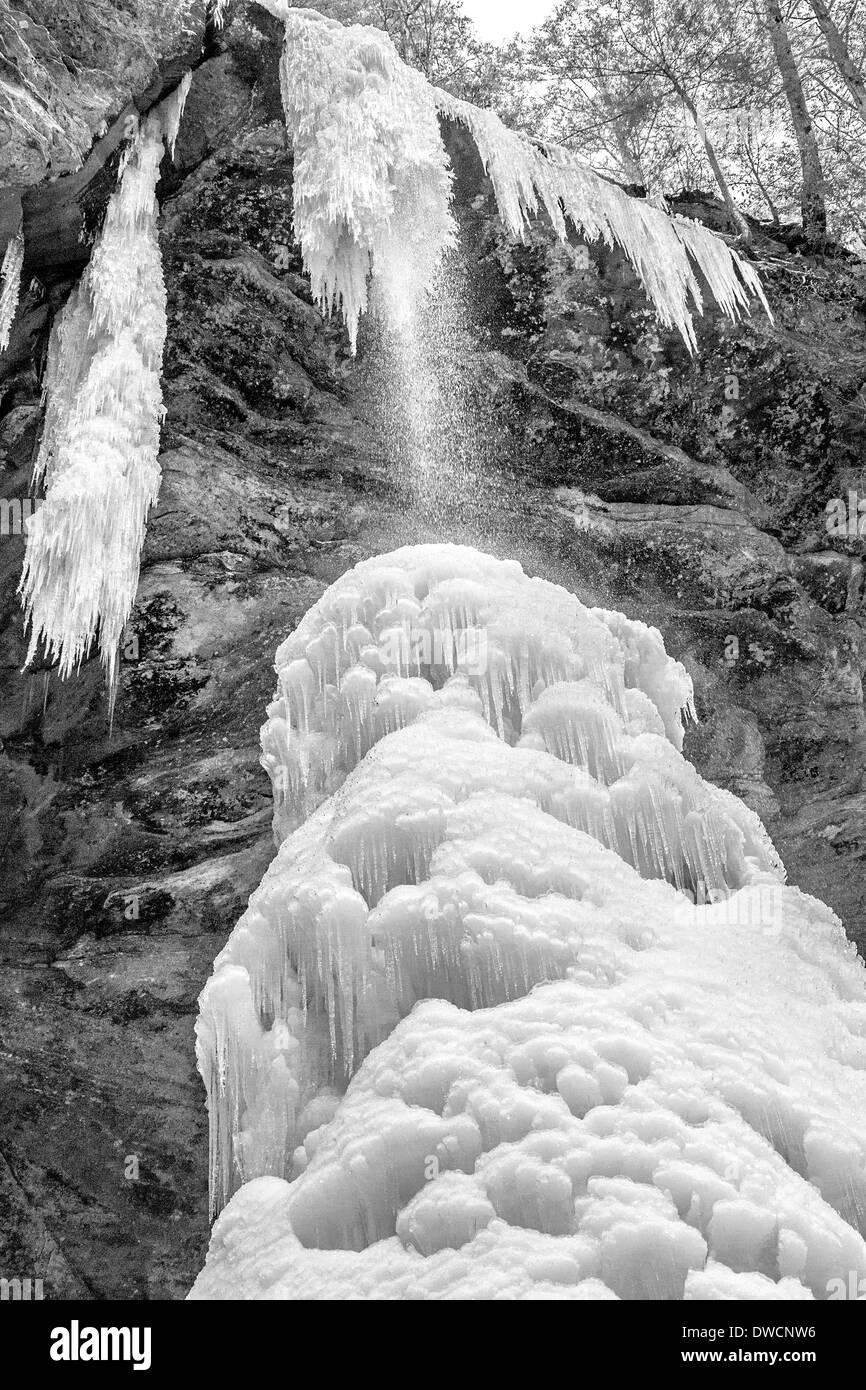 Cono de hielo gigante que se ha formado en la base de la cascada en Ash Cave, una de varias cavernas con cascadas, Hocking Hills, OH Foto de stock