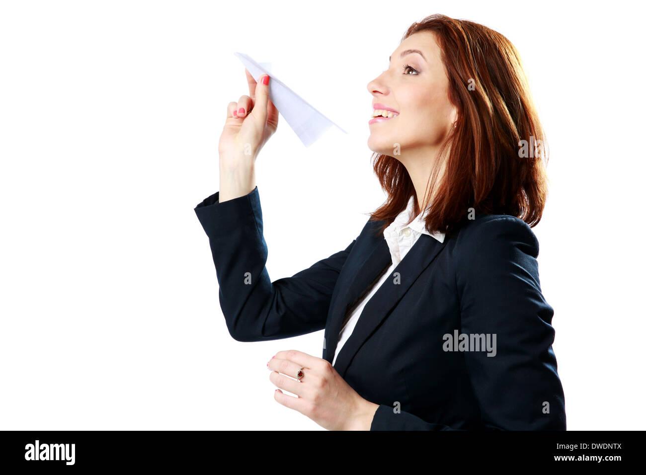 Feliz empresaria lanzando avión de papel aislado sobre un fondo blanco. Imagen De Stock