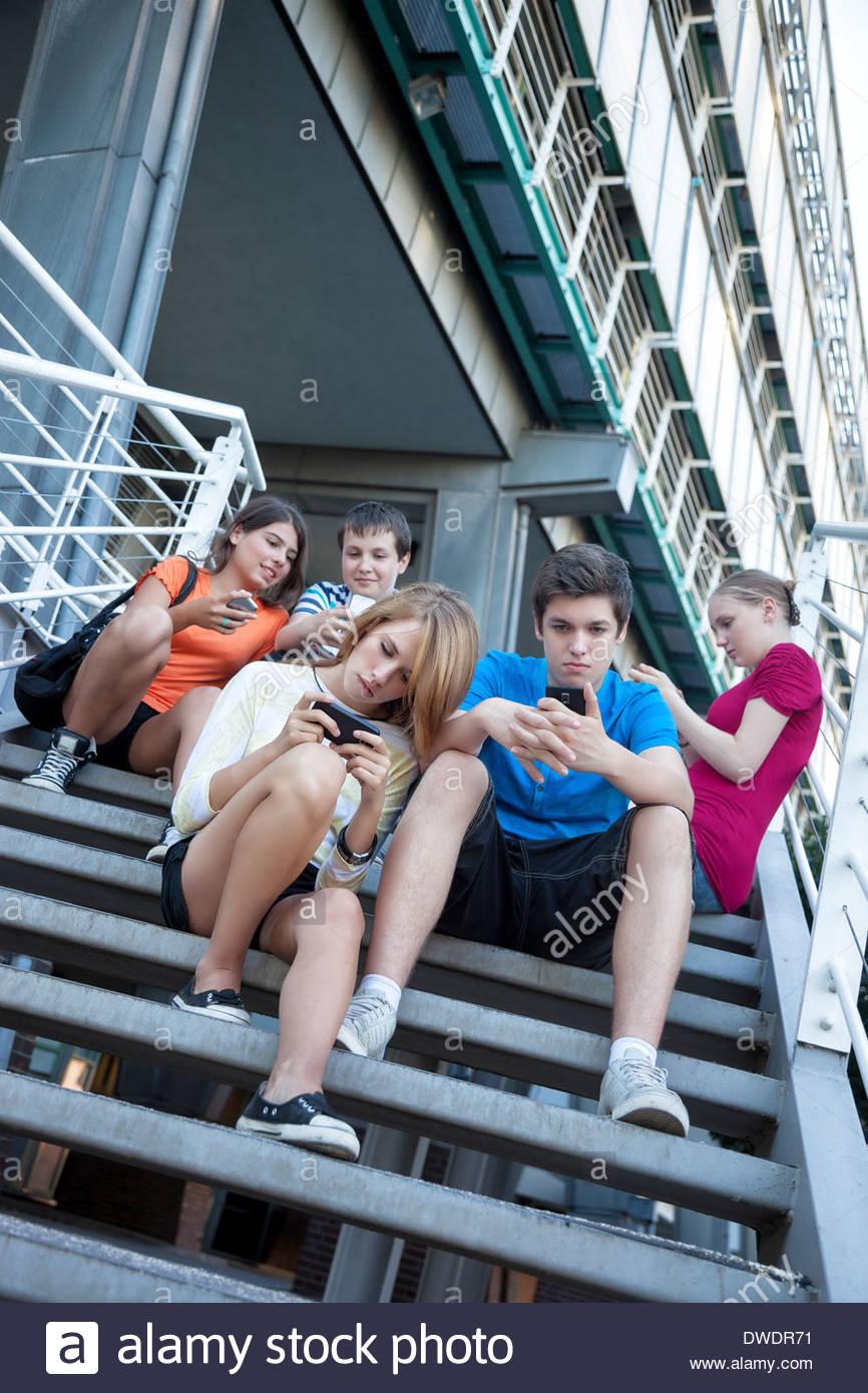 Amigos adolescentes utilizando dispositivos móviles en escaleras Foto de stock