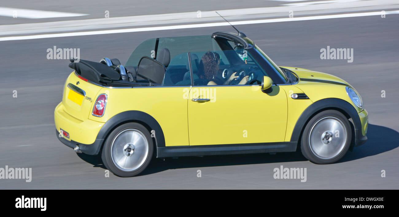 Dos puertas BMW Mini Cooper descapotable coche convertible con la mujer la conducción en autopista, Essex, Inglaterra Imagen De Stock