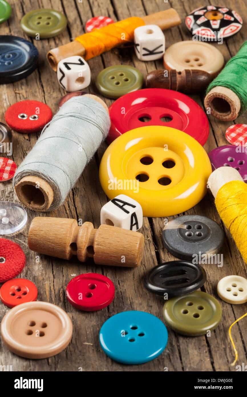 Conjunto de botones en la costura de color de fondo de madera Foto de stock