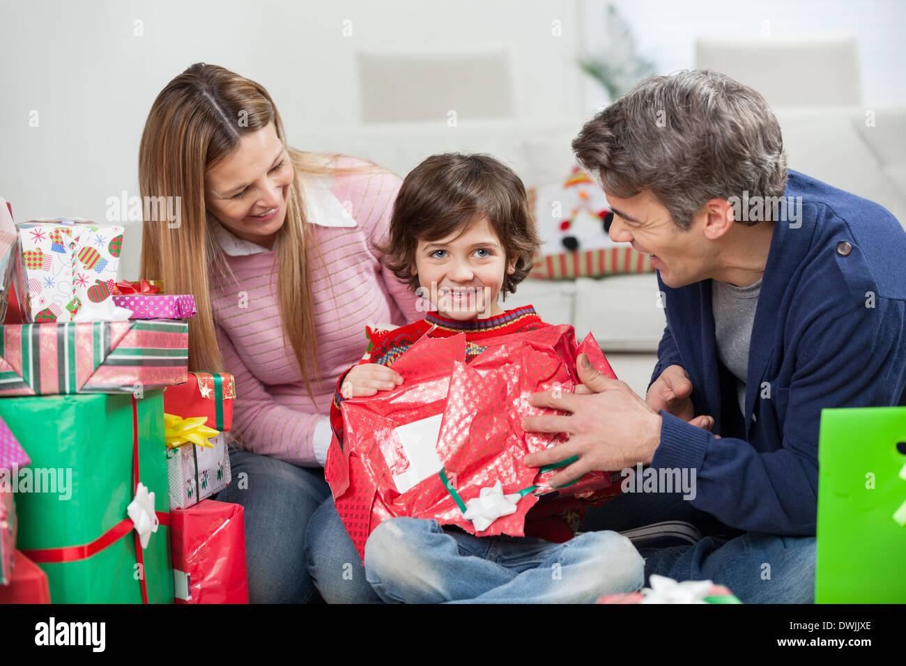 Chico y Padres Abriendo Regalo de Navidad Imagen De Stock