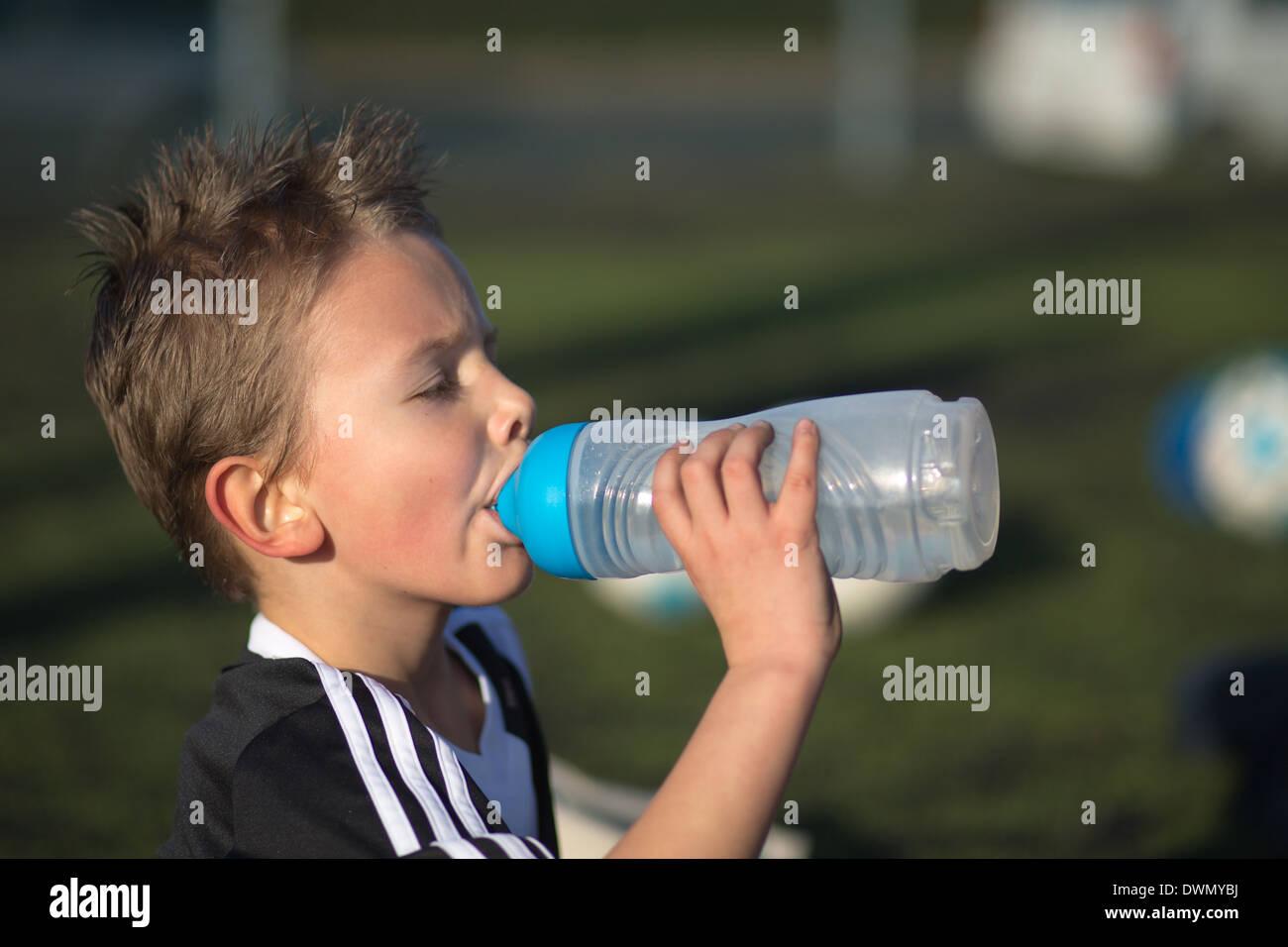 Niño bebe agua después de un partido de fútbol para niños. Imagen De Stock 071678035ce71