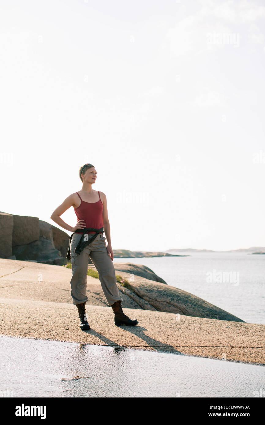 La longitud completa de la mujer en la ropa deportiva de pie sobre una roca en el mar Imagen De Stock