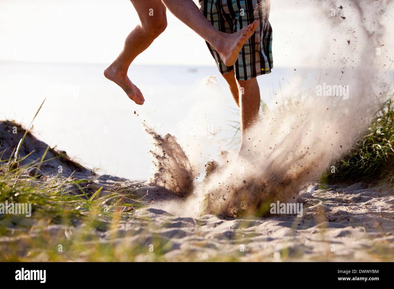 Imagen recortada de juguetones amigos varones en la playa Imagen De Stock