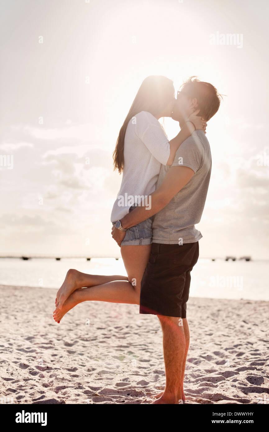 Captura del perfil de la joven pareja besándose en la playa Imagen De Stock