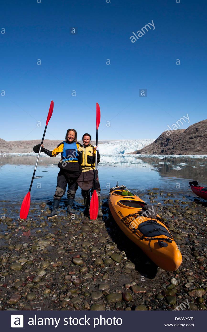 Retrato de longitud completa de mujeres maduras sosteniendo los remos de kayak en Lakeshore Imagen De Stock