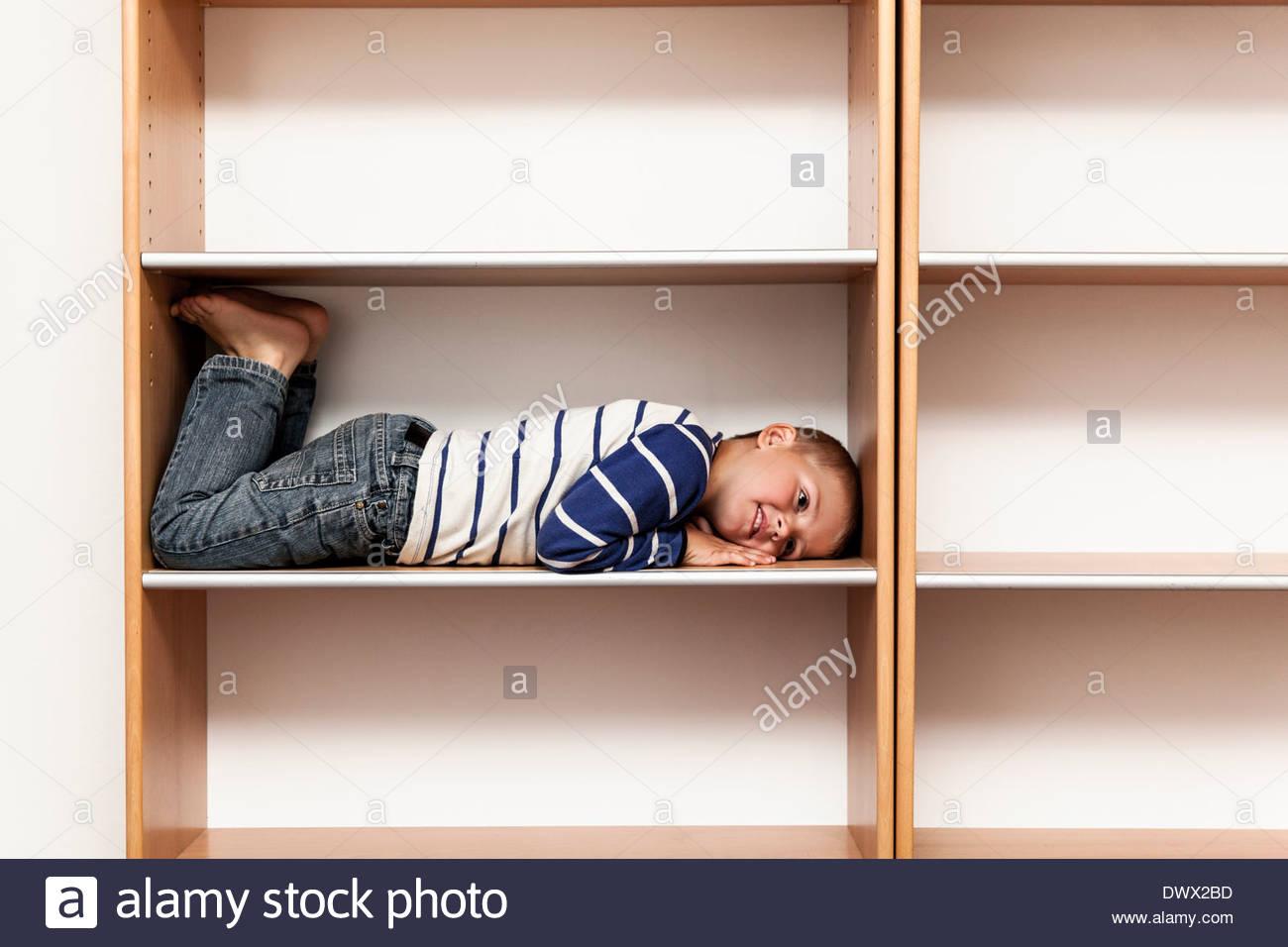La longitud total del muchacho juguetón acostado en la estantería vacía en casa Imagen De Stock