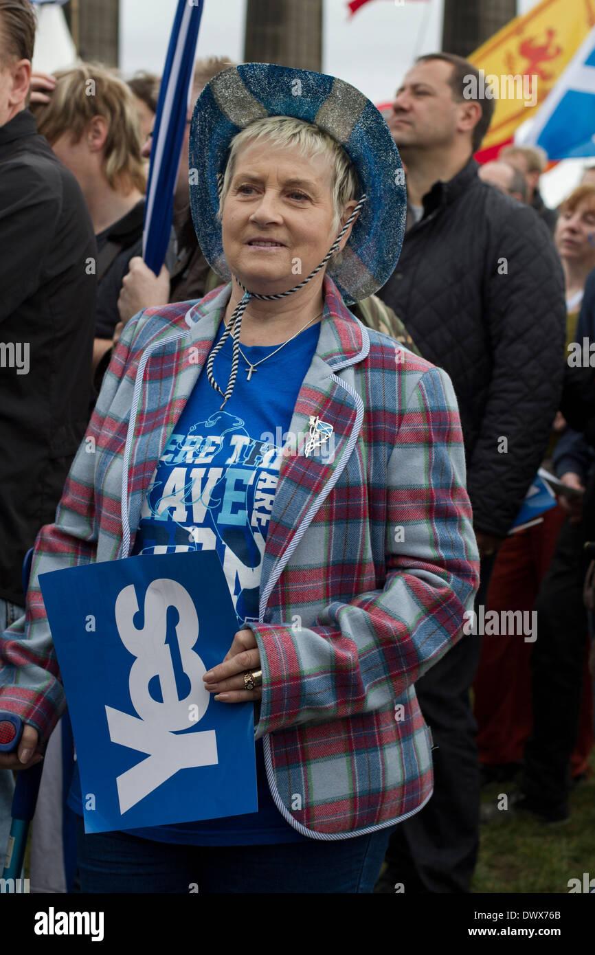 Una mujer en una chaqueta de tartán escuchar discursos durante un mitin pro-independencia en Edimburgo en 2013. Imagen De Stock