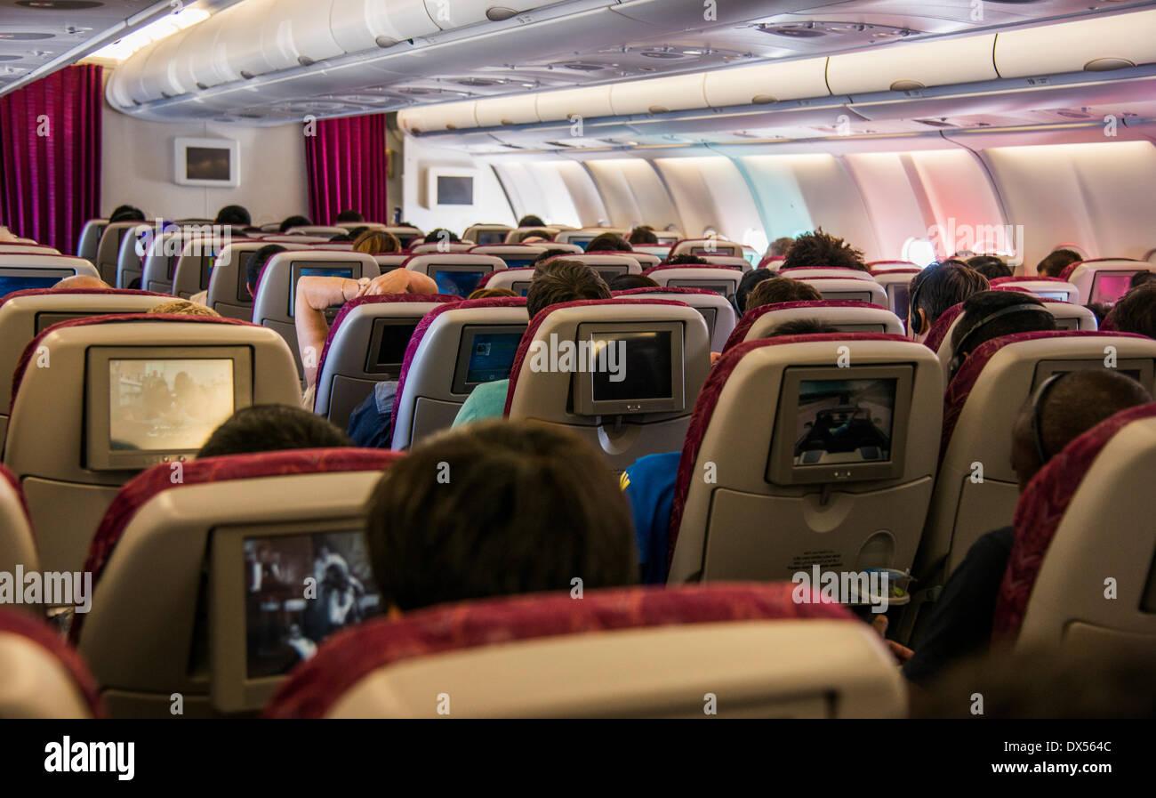 La cabina de un avión de pasajeros con pantallas de entretenimiento y los pasajeros Imagen De Stock