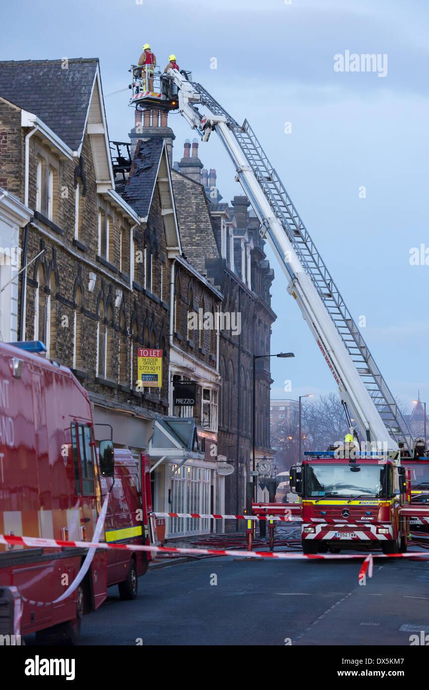 Valiente bombero tripulación en lo alto de la escalera (desde el motor) combatir el fuego con una manguera de agua, en el centro de la ciudad edificio - Harrogate, North Yorkshire, Inglaterra, Reino Unido. Foto de stock