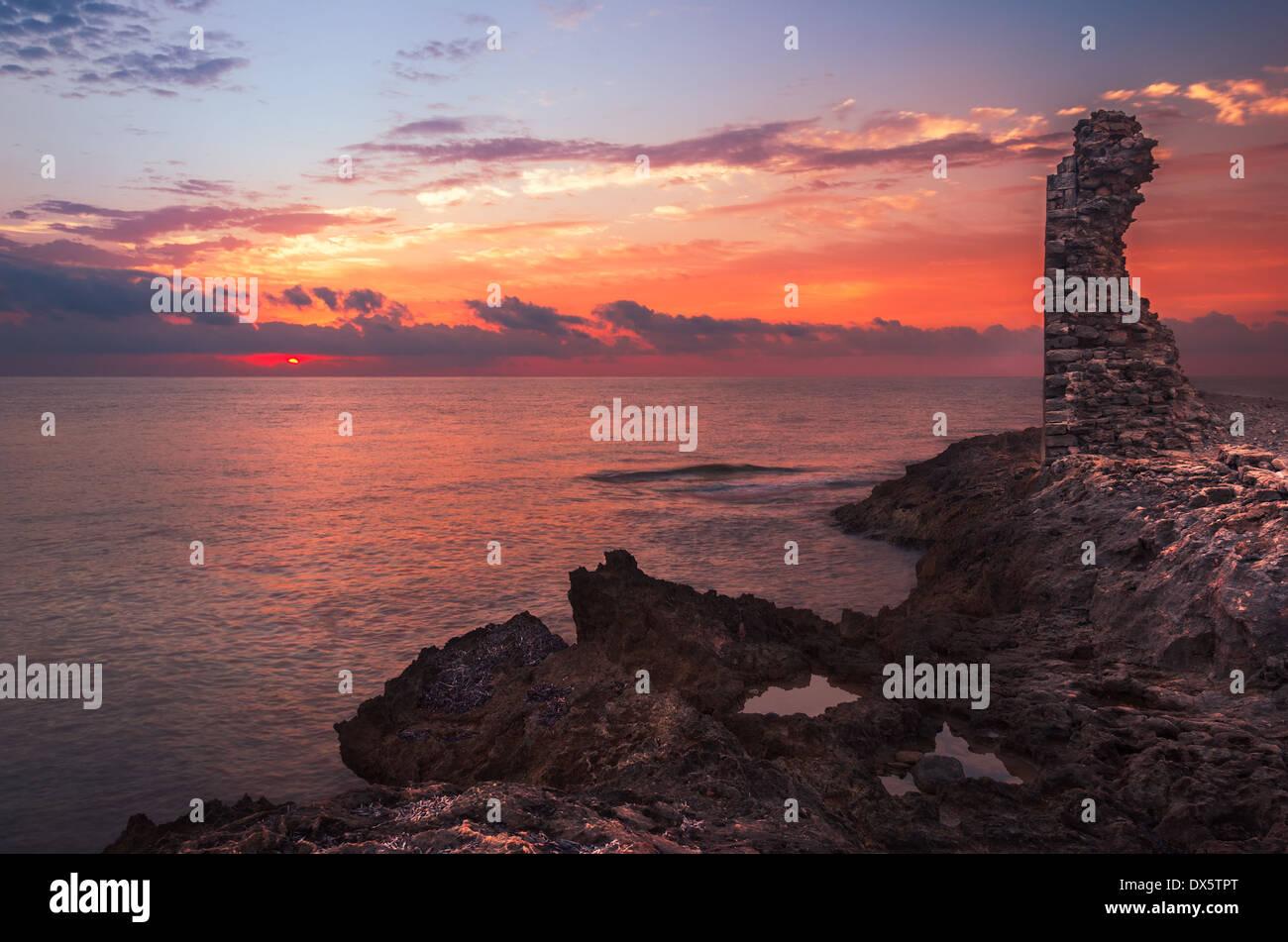 La puesta de sol sobre el mar y la costa rocosa con ruinas antiguas y puerta a África en Mahdia, Túnez Foto de stock