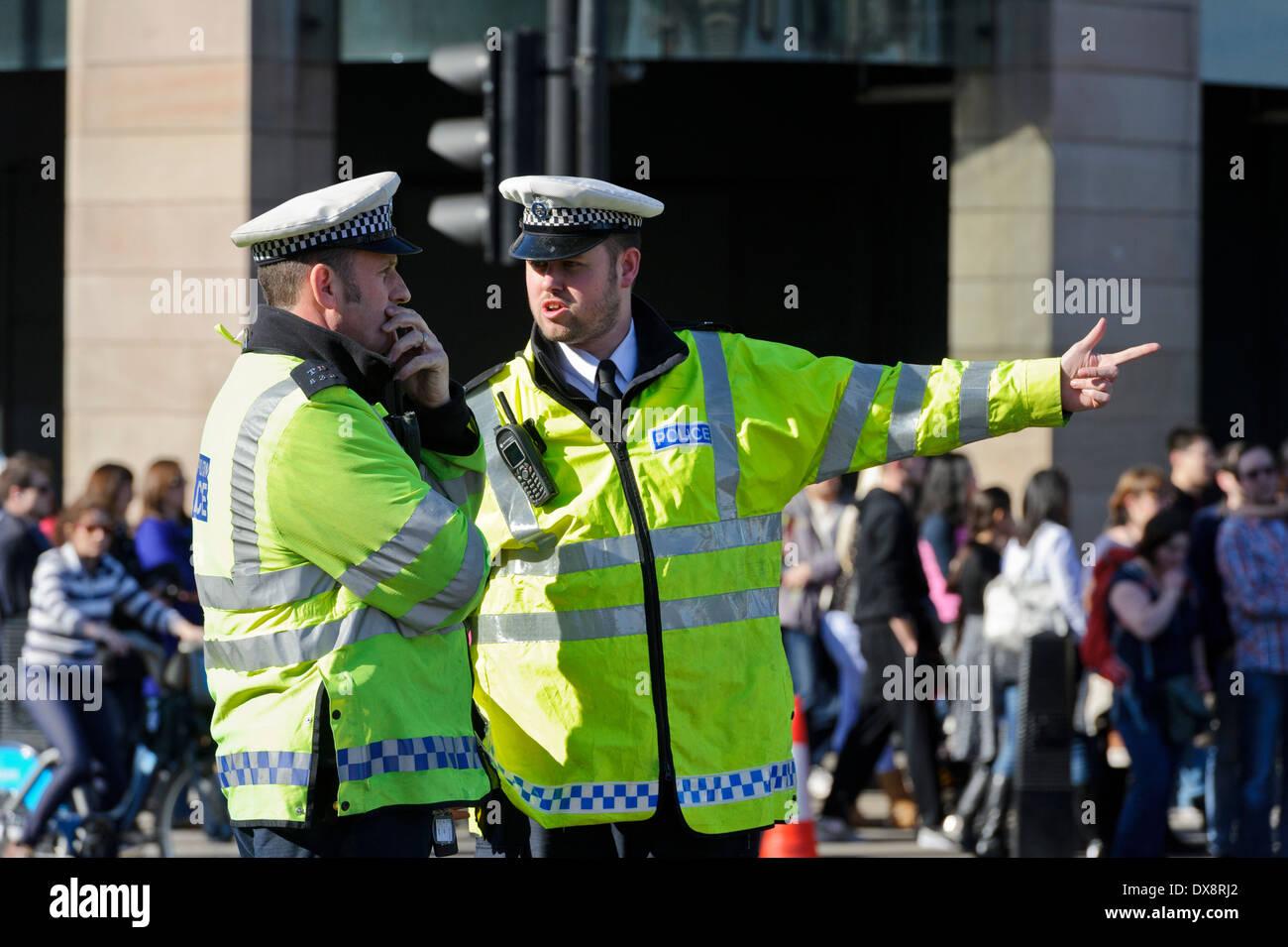 Dos funcionarios de la Policía de Tránsito Metropolitano uniforme hablando de una situación, Londres, Inglaterra, Reino Unido. Imagen De Stock