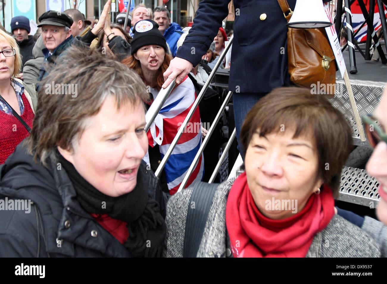 Belfast, Reino Unido, 8 de marzo de 2014. Anna Lo (derecha) de la alianza Partido en Irlanda del Norte es interpelado por un manifestante bandera leales Foto de stock