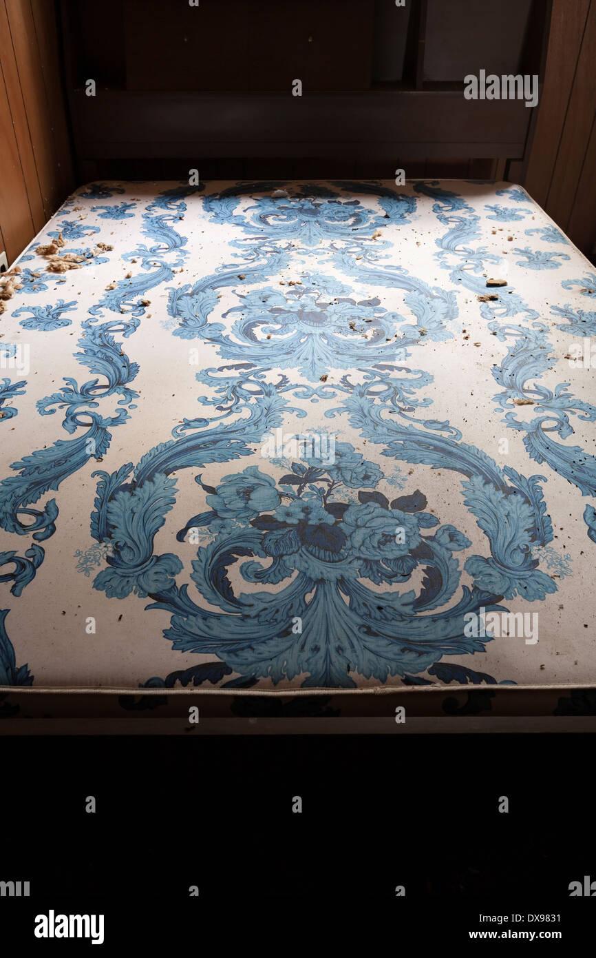 Un sucio colchón viejo en el marco de la cama encontró en una casa ...