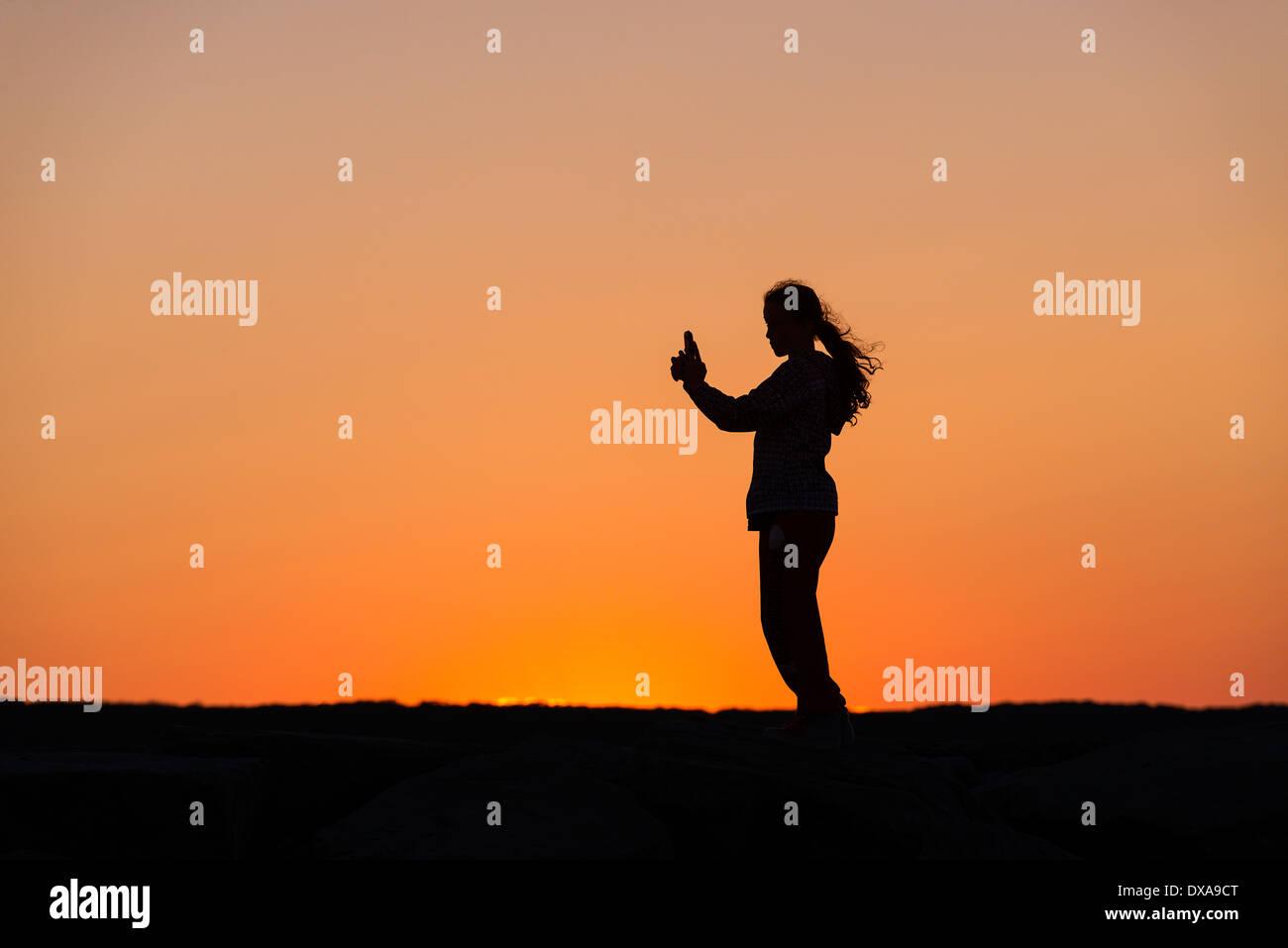 Chica con teléfono móvil disfruta de la puesta de sol desde un embarcadero. Imagen De Stock