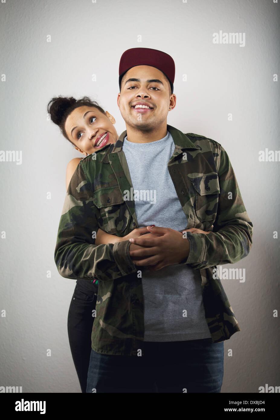 Lindo joven sosteniendo su novio desde detrás sobre fondo gris. Linda pareja joven en amor. Imagen De Stock