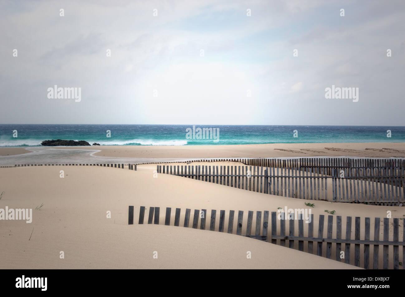 Tarifa, Cádiz, Costa de la Luz, Andalucía, España. Vallas de madera en playas azotadas por el viento y el océano Atlántico. Imagen De Stock