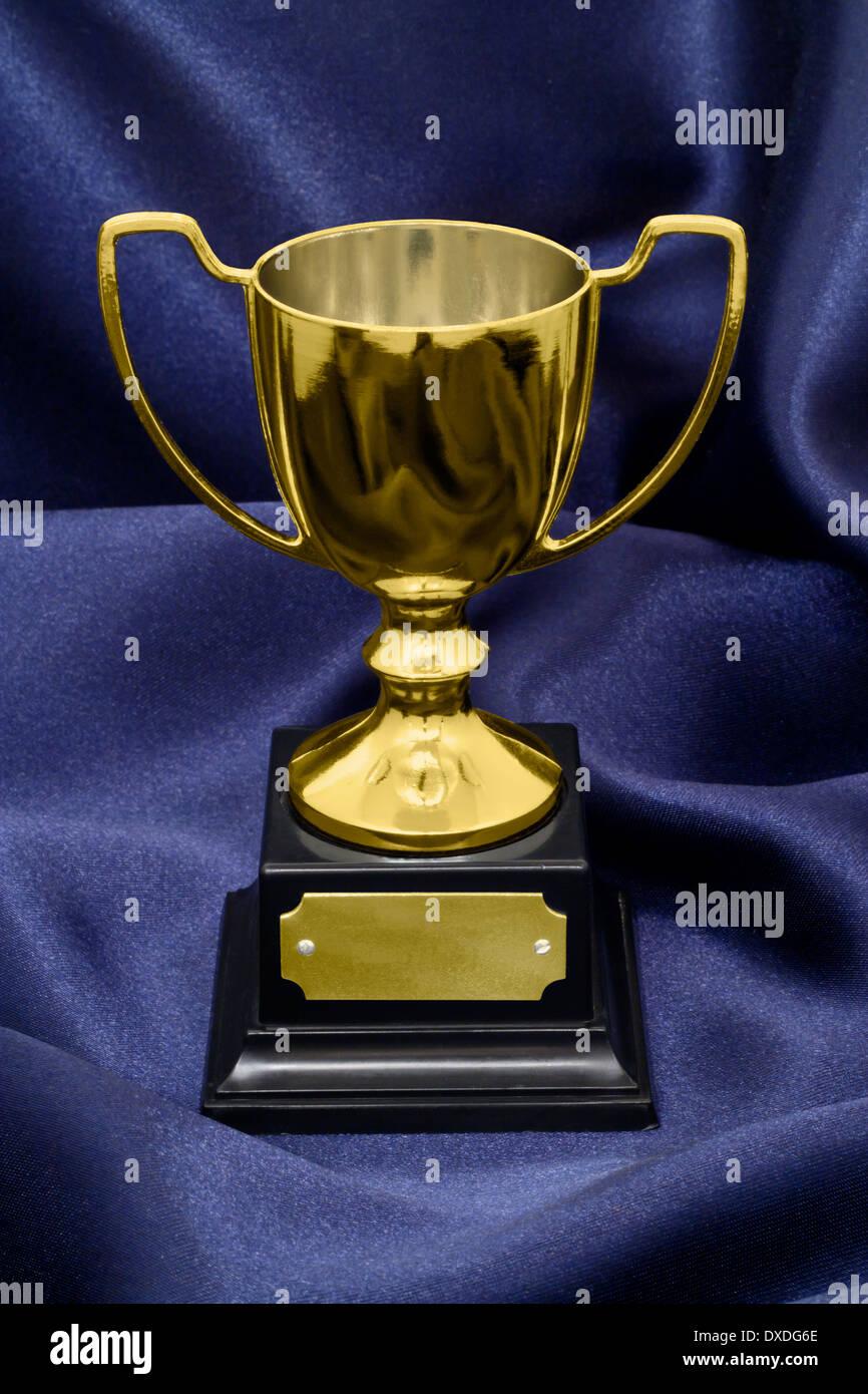 Ganadores de un trofeo de oro sobre un fondo de seda azul gran concepto de logro, éxito o ganar un concurso o premio. Imagen De Stock
